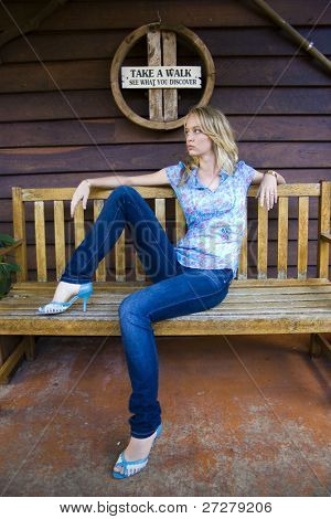 beautiful young woman on a bench with jeans and high heels