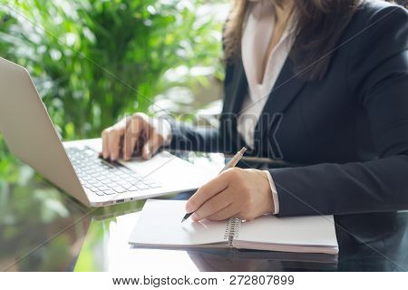 Business Woman Working With A Laptop And Writing.