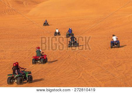 Quad Biking Dubai Adventure Tour -tourists Having Fun On Quad Bike Riding In Dunes Of Dubai. Dune Ba