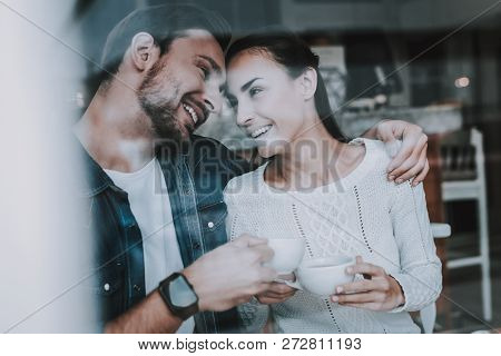 Couple Resting In Cafe. Couple Is Beautiful Young Man And Woman. People Is Drinking A Tea In Cups. P