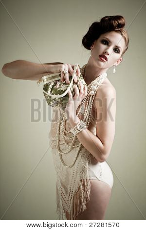 Beautiful young woman holding a vintage bag in a fashion portrait