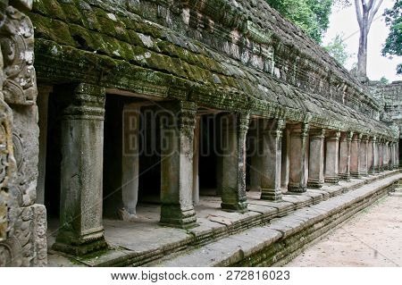 Distance. A Long Line Of Moss Covered Pillars In The Jungle Ruins Of Cambodia