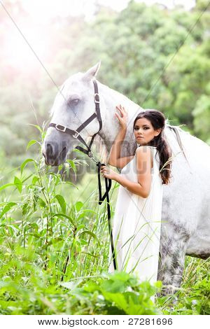 beautiful young woman with a grey horse in the rainforest poster