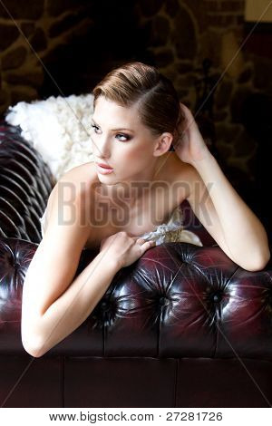 portrait of a beautiful fashion model wearing an elegant dress lying on the couch
