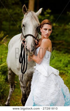 Beautiful young woman leading a grey horse in the country poster