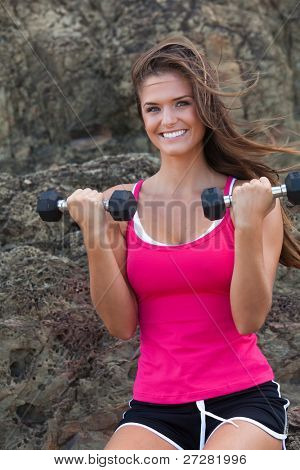 Portrait of a young woman working out with hand weights by a large rock formation. She is smiling at the camera. Vertical format.