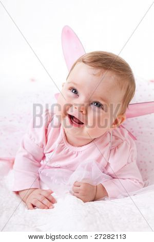 A cute baby girl in fairy wings laughs while looking up at the camera. Vertical shot.
