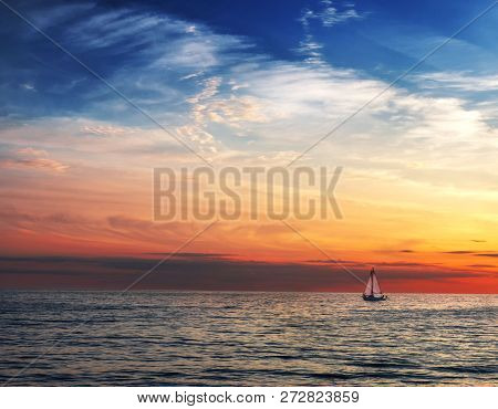 The Sailboat Sails Under The Setting Sun. Air Clouds Of Different Colors.