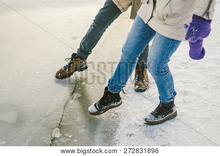 Trying the danger of the foot, testing the thin ice near the shore. A pair of lovers walk with a walk along a frozen lake to press foot on the ice poster