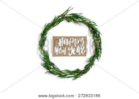 Wreath Made From Conifer Tree Branches On A White Background. Card With Handwritten Quote - Happy Ne