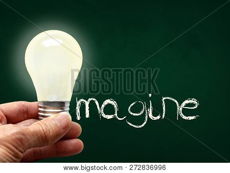 Man Holding Illuminated Bulb With Bare Hands Against Chalkboard With The Word Imagine. Concept Of Br