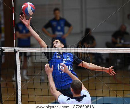 KAPOSVAR, HUNGARY – NOVEMBER 29, 2018: Kristof Horvath (with ball) in action at a Hungarian National Cup volleyball game between Kaposvar (blue) and MAV Elore (white) in Sportcsarnok Kaposvar.