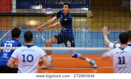 KAPOSVAR, HUNGARY – NOVEMBER 29, 2018: Kristof Horvath receives the ball at a Hungarian National Cup volleyball game between Kaposvar (blue) and MAV Elore (white) in Sportcsarnok Kaposvar.