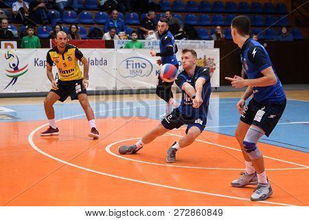 KAPOSVAR, HUNGARY – NOVEMBER 29, 2018: Bence Bozoki receives the ball at a Hungarian National Cup volleyball game between Kaposvar (blue) and MAV Elore (white) in Sportcsarnok Kaposvar.