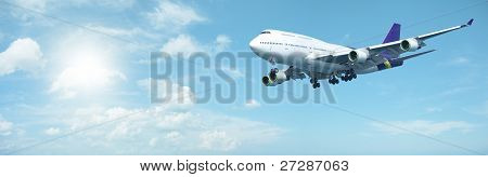 Jumbo jet aircraft is maneuvering in a sunny sky. Panoramic composition. poster