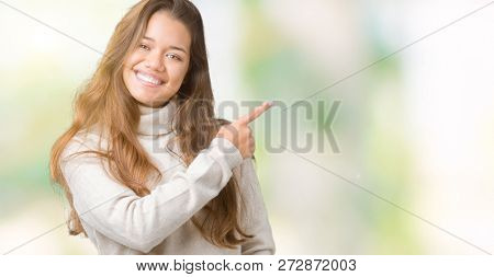 Young beautiful brunette woman wearing turtleneck sweater over isolated background cheerful with a smile of face pointing with hand and finger up to the side with happy and natural expression on face