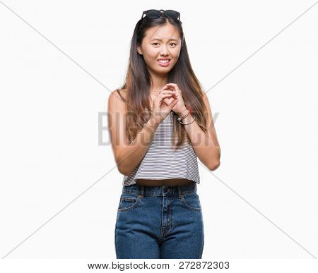 Young asian woman wearing sunglasses over isolated background disgusted expression, displeased and fearful doing disgust face because aversion reaction. With hands raised. Annoying concept.