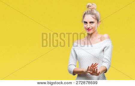 Young beautiful blonde and blue eyes woman over isolated background disgusted expression, displeased and fearful doing disgust face because aversion reaction. With hands raised. Annoying concept.