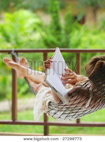 Young woman lying in a hammock in garden and reading a book
