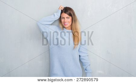 Young adult woman over grey grunge wall wearing winter outfit confuse and wonder about question. Uncertain with doubt, thinking with hand on head. Pensive concept.