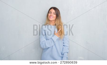 Young adult woman over grey grunge wall wearing winter outfit cheerful with a smile of face pointing with hand and finger up to the side with happy and natural expression on face looking at the camera