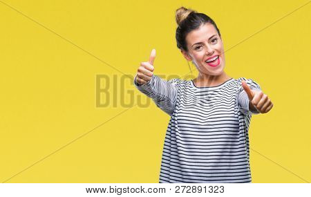 Young beautiful woman casual stripes sweater over isolated background approving doing positive gesture with hand, thumbs up smiling and happy for success. Looking at the camera, winner gesture.
