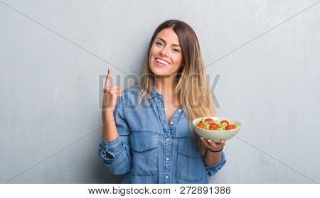 Young adult woman over grey grunge wall eating healthy tomato salad surprised with an idea or question pointing finger with happy face, number one