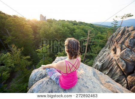 Aerial View Of Lit By Summer Sun Young Slim Sporty Woman Sitting On Top Of Huge Rock, Doing Yoga On