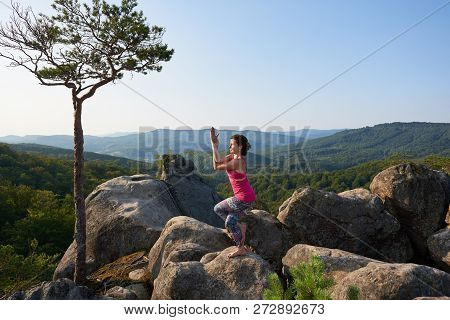 Attractive Girl Stands In Complicated Yoga Pose On Top Of Big Rock On Mountains Covered With Forest