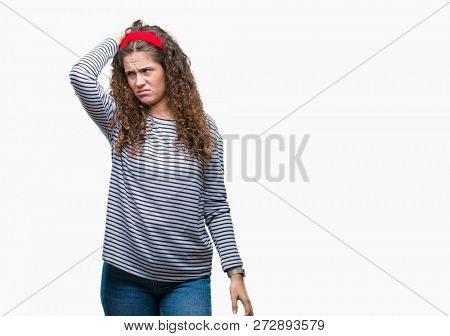 Beautiful brunette curly hair young girl wearing stripes sweater over isolated background confuse and wonder about question. Uncertain with doubt, thinking with hand on head. Pensive concept.
