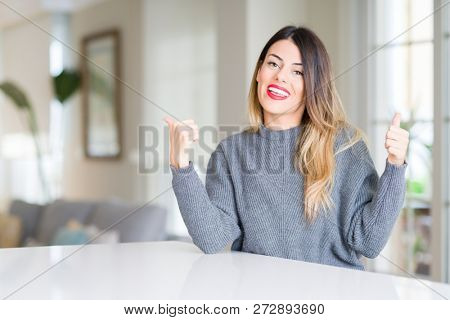 Young beautiful woman wearing winter sweater at home success sign doing positive gesture with hand, thumbs up smiling and happy. Looking at the camera with cheerful expression, winner gesture.