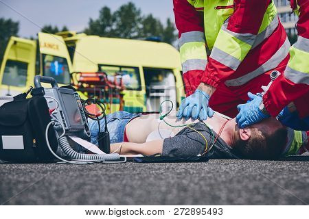 Cardiopulmonary Resuscitation. Rescue Team (doctor And A Paramedic) Resuscitating The Man On The Roa