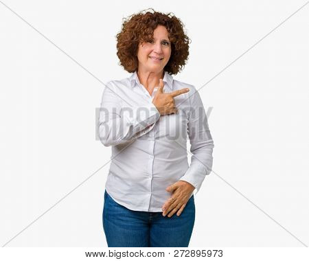 Beautiful middle ager senior businees woman over isolated background cheerful with a smile of face pointing with hand and finger up to the side with happy and natural expression on face