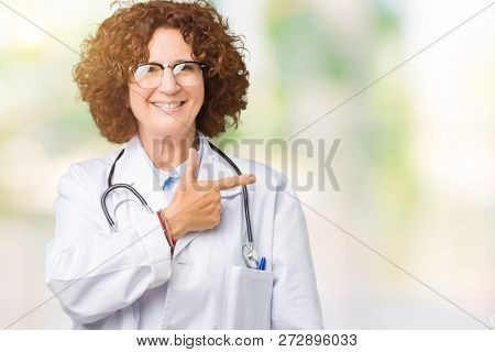 Middle ager senior doctor woman over isolated background cheerful with a smile of face pointing with hand and finger up to the side with happy and natural expression on face