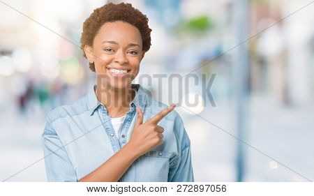 Young beautiful african american woman over isolated background cheerful with a smile of face pointing with hand and finger up to the side with happy and natural expression on face
