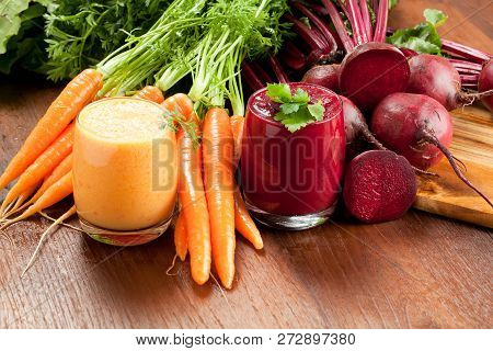 Mix Beetroot And Carrot Juices On Wooden Background.