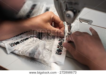 Female Seamstress Hands Connecting White Fabric Details With Floral Colorful Embroidery With Stripes
