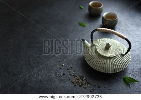 Teapot And Teacups On Black Table