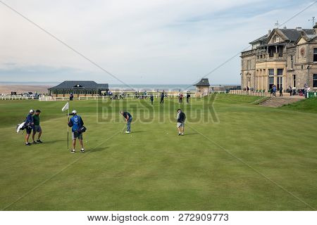 St Andrews, Scotland - May 21, 2018: Man Putting A Ball At 18 Th Hole Near Famous Clubhouse Golf Cou