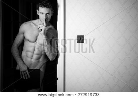Naked Man With Muscular Body Standing In Doorway Covering Himself With Book While Holding A Finger T