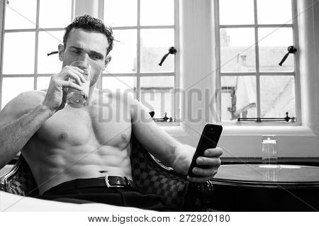 Handsome Shirtless Man With Muscular Pecs And Six Pack Abs Using Mobile Phone And Drinking Juice