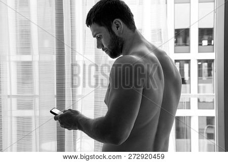 Good Looking, Muscular Shirtless Man Using Mobile Phone Next To Balcony With City View
