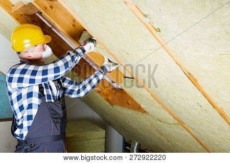 Man Installing Thermal Roof Insulation Layer - Using Mineral Wool Panels. Attic Renovation And Insul