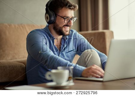 Young man with headphones using laptop in his home