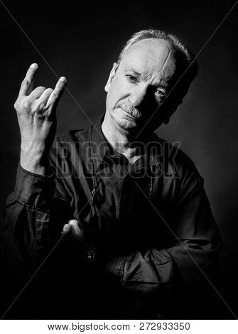 Black And White Portrait Of An Old Man Gesturing On Dark Background. Elderly Old Man Shows With Fing