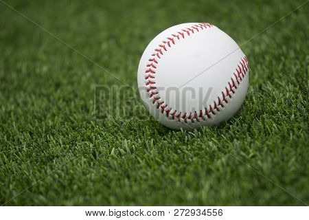 This Is An Image Of A Baseball Laying On Grass