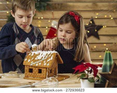 Photo Of A Young Brother And Sister Decorating A Gingerbread House At Home Just Before Christmas.