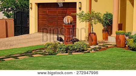 Nice Patio In A Residential Area With A Green Lawn, A House, A Gate And A Garage In The Background.