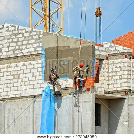 Construction. Urban Landscape. Group Of Builders In Hard Hats With Plastering Tools Plaster A Wall I