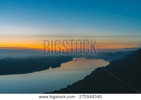 View from high shore on broad river. Riverbank with forest under thick fog. Dawn reflected in water. Yellow glow in picturesque predawn sky. Mystical morning atmospheric landscape of majestic nature. poster